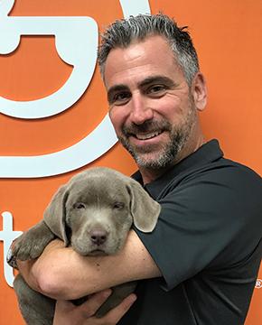 Alex Samios Holding Puppy