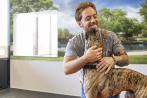 Dogtopia worker hugging a dog and getting licked