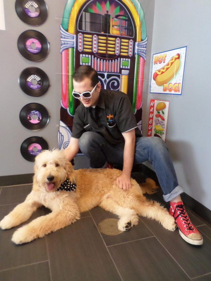 Time Warp Tuesdays. Bentley the Goldendoodle with our team member Erik posing in our Rock N' Roll Photo Booth Set up