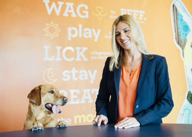 Owner dropping-off a dog at Dogtopia of South Austin reception desk.