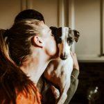 a woman kissing a dog